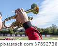 Man with glasses playing the trumpet into the sky 37852738