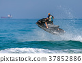 A man on a water motorcycle on the sea 37852886