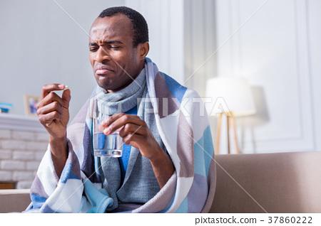 Cheerless unhappy man taking medicine 37860222