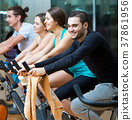 Active adults riding stationary bicycles 37861956