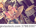 Happy teenage girl shopping drum kit 37863087