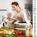 mother and daughter using multicooker 37863111