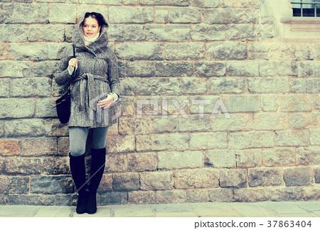 cheerful female in coat hood near wall 37863404