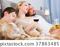 Happy parents with sleeping son watching TV 37863485
