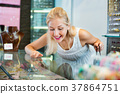 Portrait of young woman standing next to glass showcases 37864751