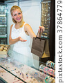 Woman seller standing in jewellery boutique 37864779