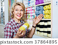 Mature glad woman customer picking various yarn 37864895