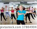 glad men women posing in fitness studio 37864904