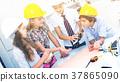 Children in helmet talking about building 37865090