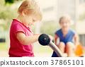 Two happy little sisters on teetering board 37865101
