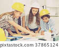 Children in helmet talking about building 37865124