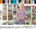 portrait of female cashier standing at cash desk in embroidery shop 37865217