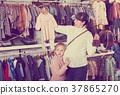 Pregnant woman examining baby's clothes 37865270