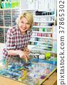 Mature woman near glass showcase in boutique. 37865302