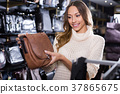 Ordinary female choosing bag among assortment 37865675