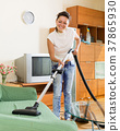woman hoovering apartment 37865930