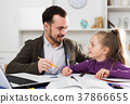 Father helping daughter with homework 37866655