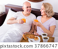 Mature couple having breakfast in bed. 37866747