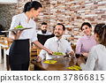Female waiter bringing order to visitors in country restaurant 37866815