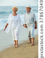 cheerful pensioners walking barefoot together 37867049