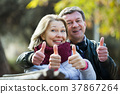 Mature couple with thumbs up in park 37867264