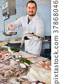 Man in glove behind counter shows fish in his hand 37868046