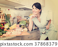 Cheerful woman is posing in time cooking on the kitchen 37868379