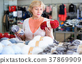 Mature woman buyer choosing colored yarn for knitting on sale 37869909