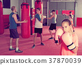 Girl with boxing gloves posing in defended stance 37870039