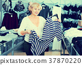 Happy woman consumer choosing striped dress 37870220