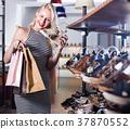 girl choosing pair of shoes in store . 37870552