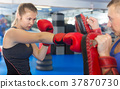 man is training with woman and punching gloves in box gym. 37870730