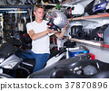 Man is choosing helmet for motorbike 37870896