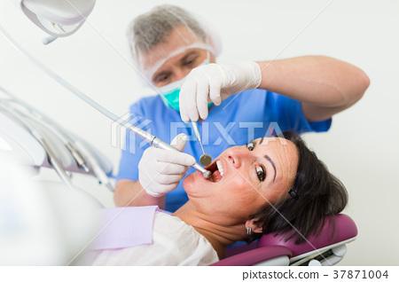 dentist professional filling teeth 37871004