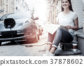 Joyful lady waiting for her charging in city 37878602