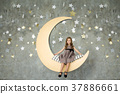Happy Little girl sits on a yellow moon.  37886661