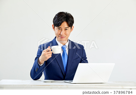 Twenty-something business man sitting and working on a laptop 37896784