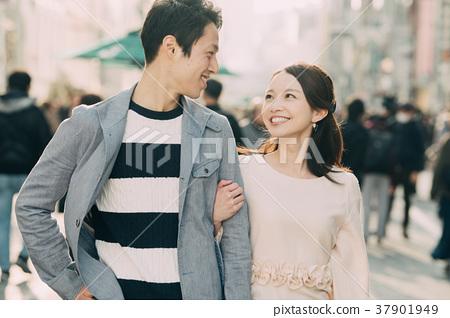 走與胳膊的年輕夫婦橫渡了微笑 37901949