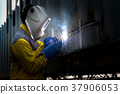 worker with welding steel to repair container 37906053