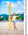 Little adorable girl playing beach volleyball with 37914650