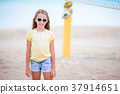 Little adorable girl playing beach volleyball 37914651