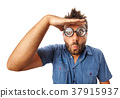Man with funny expression and thick glasses looking far away. 37915937