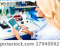 Young attractive woman scientist using tablet computer in the la 37940092