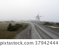 Old windmill by roadside in the mist 37942444