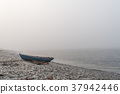 Lone landed rowboat by seaside 37942446