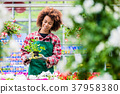Dedicated woman holding a potted plant during work 37958380