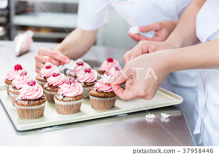 Women in pastry bakery working on muffins 37958446