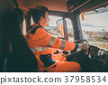Garbage removal worker driving a dump truck  37958534