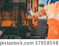 Worker emptying dustbin into waste vehicle 37958548