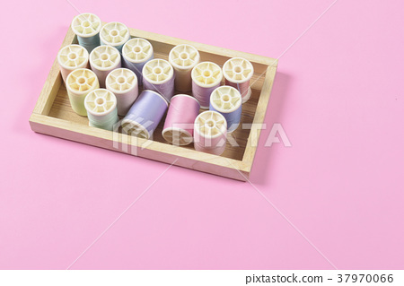 Colored thread rolls for sewing on pink background 37970066